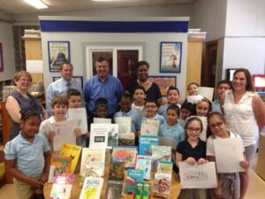 Rob and Ryan at Pottenger Elementary School Library with children staff and books