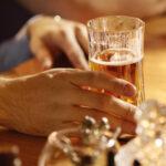 man drinking beer at bar